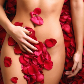 Part of the naked beautiful suntanned female body in petals of scarlet roses